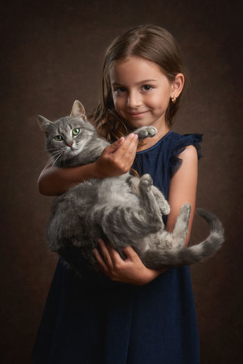 Portrait of smiling girl holding cat