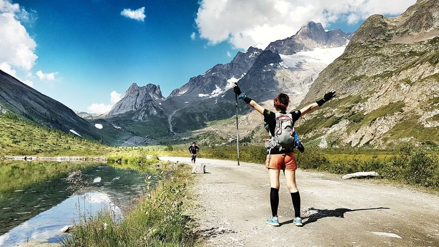 Rear view of woman with arms outstretched standing on footpath against mountains
