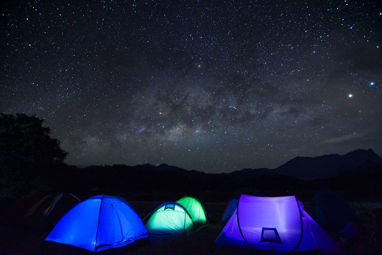 Illuminated tents on mountain against sky at night