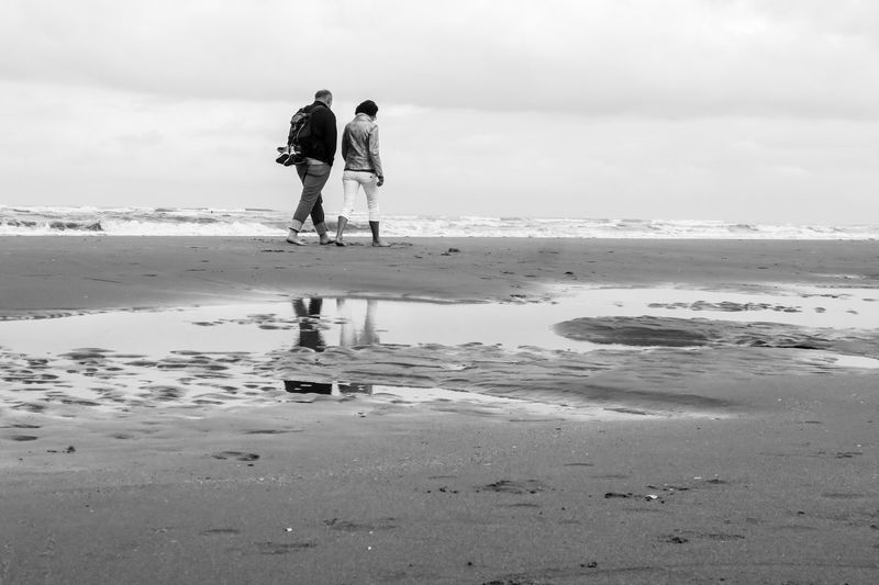 Walking at the shoreline Beach Beauty In Nature Bonding Friendship Full Length Men Nature Outdoors People Real People Rear View Sand Sea Sky Togetherness Two People Vacations Walking Water Women