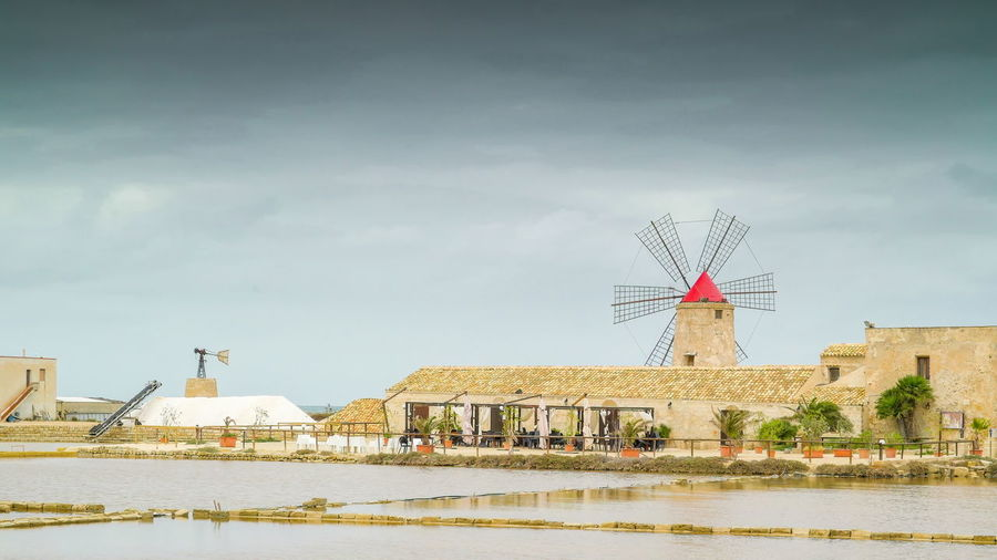 Traditional windmill by building against sky