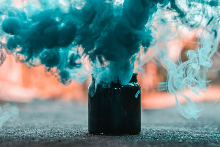 Close-up of turquoise smoke emitting from container on street