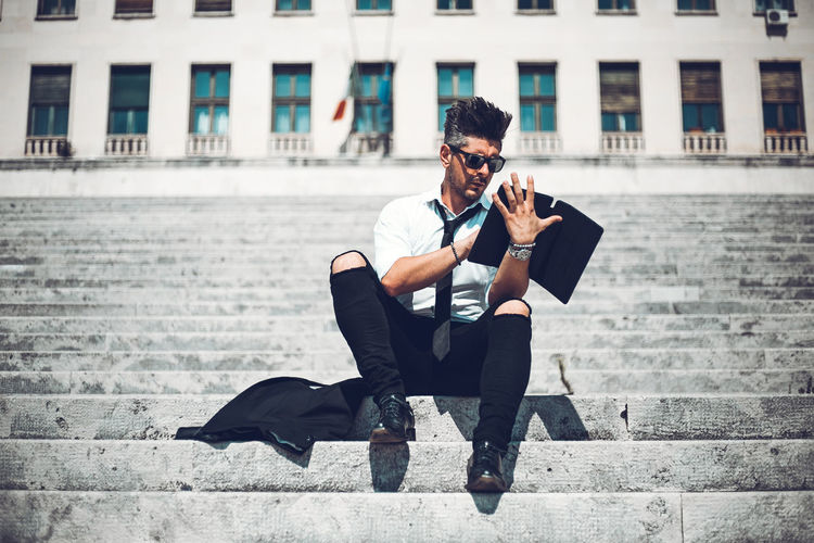 Full length of man using digital tablet while sitting on staircase in city
