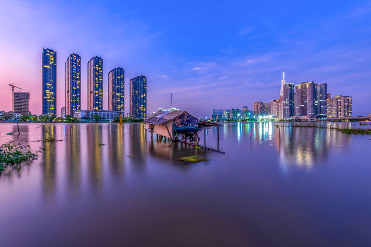 Illuminated buildings by lake against sky in city at dusk