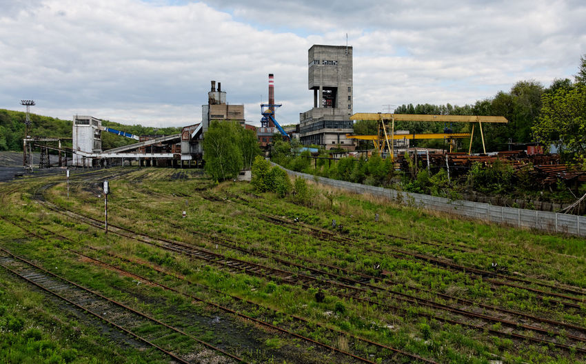 An old coal mine in Poland. Coal Mine Poland Architecture Building Exterior Built Structure Cloud - Sky Day Factory Grass Green Color History Industry Landscape Nature No People Old Old Coal Mine Outdoors Plant Rail Transportation Railroad Track Sky Track Transportation