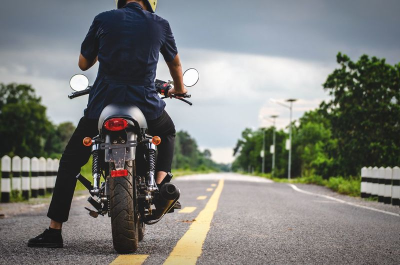 Rear view of man riding motorcycle on road against cloudy sky