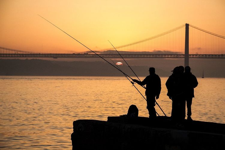 Silhouette of men fishing by sea during sunset