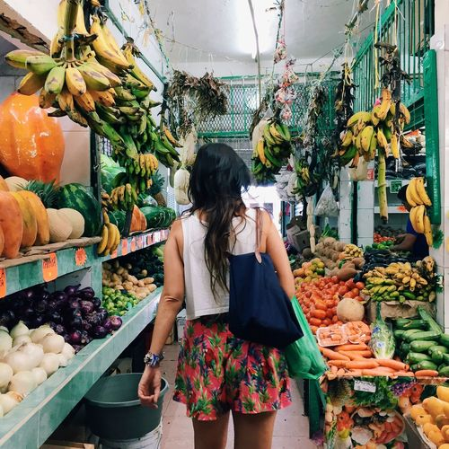 Rear view of woman in vegetable shop