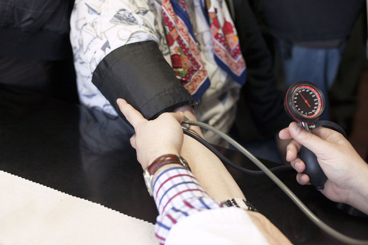 Cropped image of doctor examining patient blood pressure in hospital