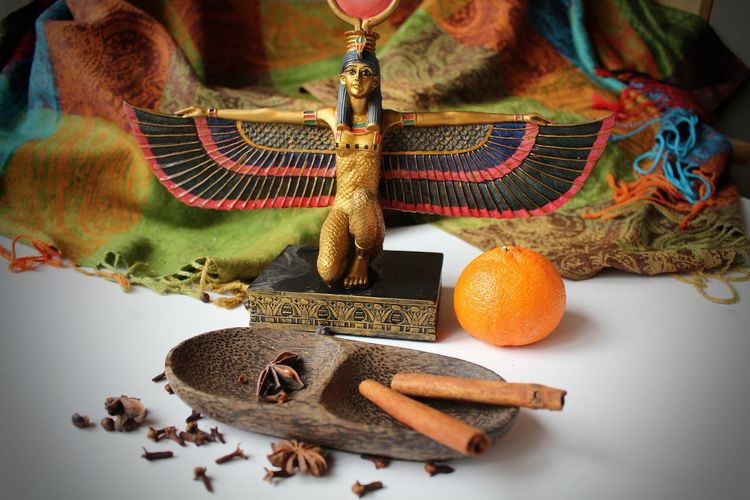Egyptian Gods Eset Goddess Isis Goddess Statue Art And Craft Celebration Cinnamon Close-up Craft Creativity Decoration Egyptian Goddess Food Food And Drink High Angle View Human Representation Indoors  No People Object Religion Representation Still Life Studio Shot Table Tangerine The Still Life Photographer - 2018 EyeEm Awards EyeEmNewHere