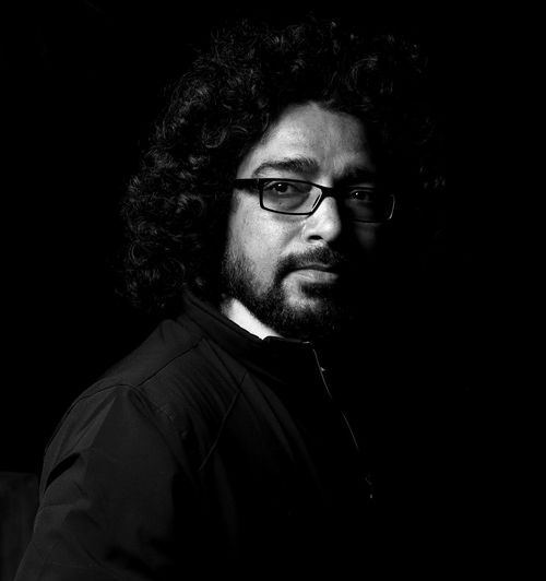 indian yoga instructor Yoga Yoga Pose Indian Real People One Person Beard Studio Shot Portrait Eyeglasses  Looking At Camera Black Background Headshot Indoors  Facial Hair Front View Men Young Men Glasses Mid Adult Adult Young Adult Hairstyle Contemplation