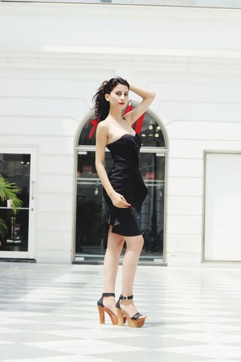 Full length portrait of woman wearing black dress and high heels standing on floor