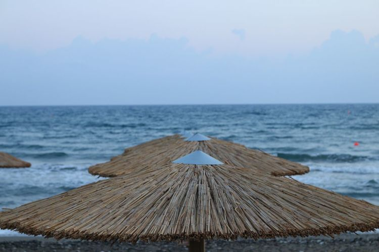 Cyprus Limassol Sea Seaside Beachphotography Wave Water Sea Thatched Roof Sky Scenics - Nature Tranquil Scene Beauty In Nature Nature Horizon Over Water Tranquility Land No People Beach Horizon Day Roof Wood - Material Focus On Foreground Outdoors