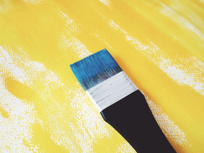 Close-up of paintbrush on yellow canvas