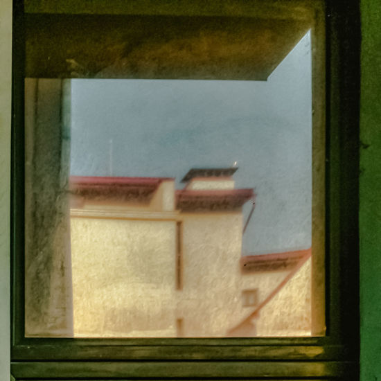 Reflection of window on glass wall of house