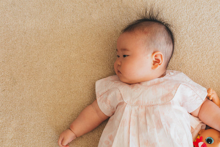 High angle view of cute baby lying on bed
