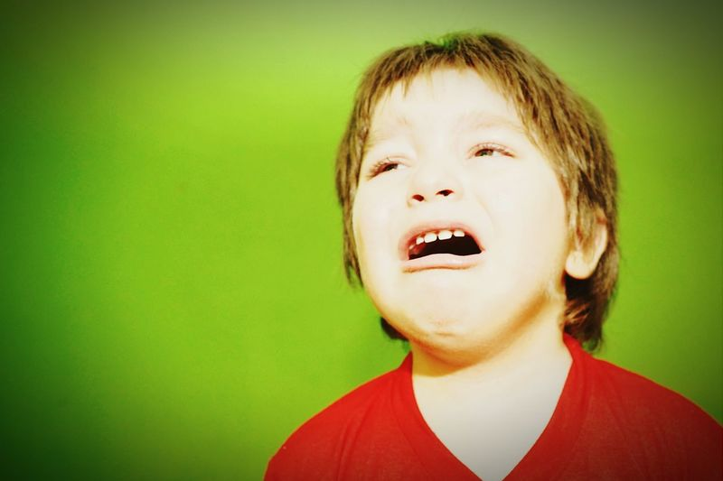 Close-up of boy crying against green background