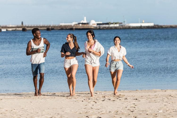 Full length of people running on beach against sky