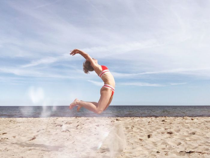 Side View Of Bikini Woman Jumping At Sandy Beach Against Cloudy Sky