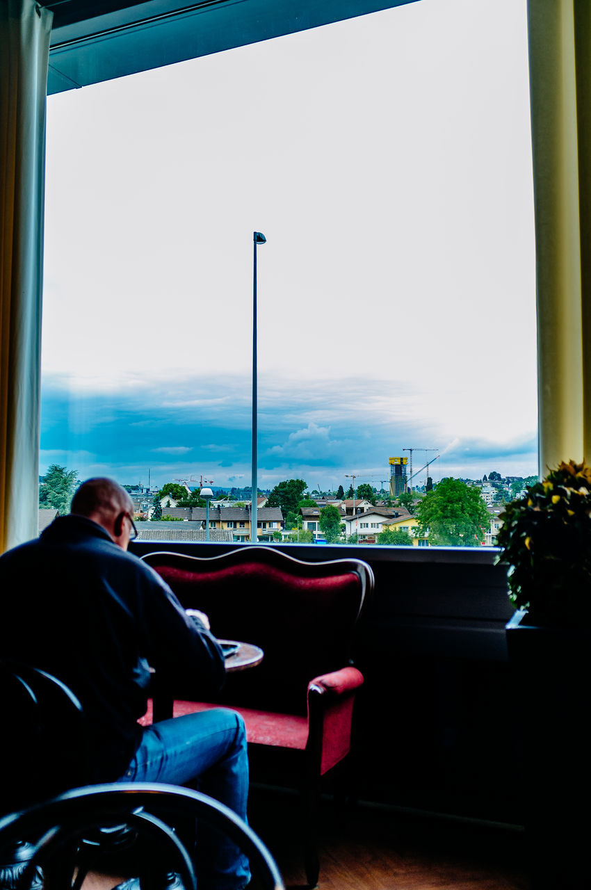 sitting, transportation, sky, window, real people, one person, mode of transport, indoors, day, looking through window, vehicle seat, tree, men, architecture, nature, city, wheelchair, people