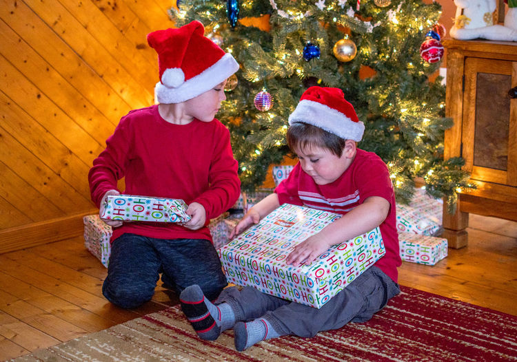 two young boys in Santa hats, examine gifts under the Christmas tree as they try to guess whats inside Christmas Child Celebration Childhood Gift Holiday christmas tree Tree Two People Santa Hat Family Decoration Positive Emotion Brothers Fun Holiday Seasonal Caucasian Ethnicity Gifts Santa Hats Excited Kid Boys Indoors  Home Interior