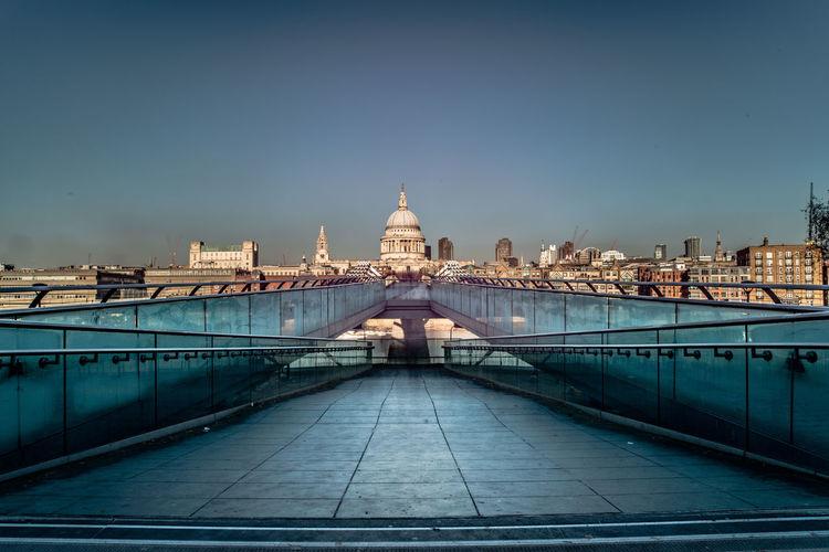 Millennium bridge, london. bridge over buildings in city against clear sky