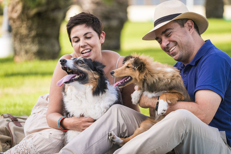 Couple playing with dogs while sitting at public park