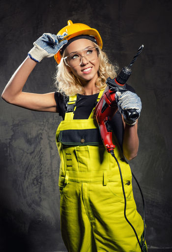 Smiling female worker holding drill while standing against wall