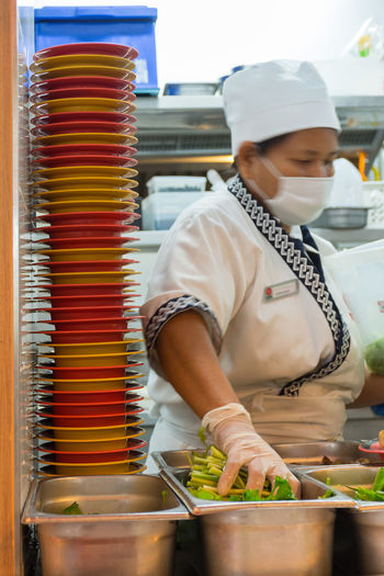 Cap Commercial Kitchen Day Expertise Factory Food Food And Drink Freshness Headwear Indoors  Occupation One Person People Real People Skill  Small Business Textile Working Workshop Young Adult Young Women