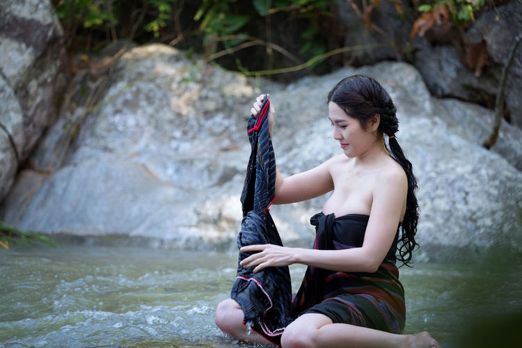 Young woman holding cloth on stream at forest