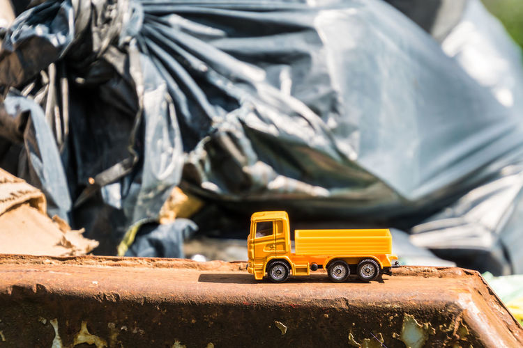Close-Up Of Toy Truck On Retaining Wall By Garbage Bags