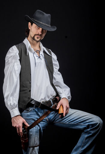 Handsome young man. This is an American cowboy. A vow to a white shirt, brown waistcoat and blue jeans. Black shoes on the feet. Carries a shtyapa, on a belt two pistols. The hair is of medium length; on the face is a beard and mustache. Authentic photo. Culture of America. Cowboy Wild West America American Gun National Authentic Moments Lifestyles Lifestyle One Person Candid Authentic Hat Jeans Man Males  Portrait Reconstruction Texas Western Gunslinger  People Real People Standing Looking At Camera