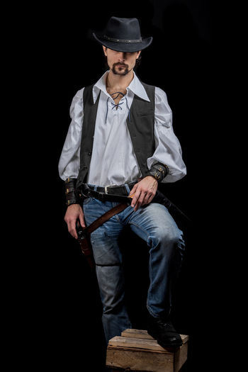 Handsome young man. This is an American cowboy. A vow to a white shirt, brown waistcoat and blue jeans. Black shoes on the feet. Carries a shtyapa, on a belt two pistols. The hair is of medium length; on the face is a beard and mustache. Authentic photo. Culture of America. Cowboy Wild West America American Gun National Authentic Moments Lifestyles Lifestyle One Person Candid Authentic Hat Clothing Front View Black Background Full Length Standing Men Young Men Young Adult Three Quarter Length Portrait Real People Jeans