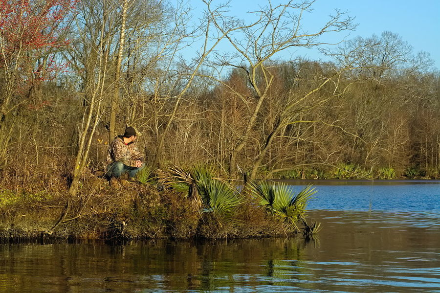 Fishing on the Alabama River Creekside Alabama River Bare Tree Beauty In Nature Catoma Creek Alabama Childhood Day Full Length Lake Man Fishing Nature One Person Outdoors People Real People Reflection Sky Tree Water Waterfront