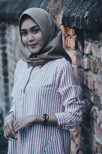 Portrait of smiling young woman wearing hijab while standing against brick wall