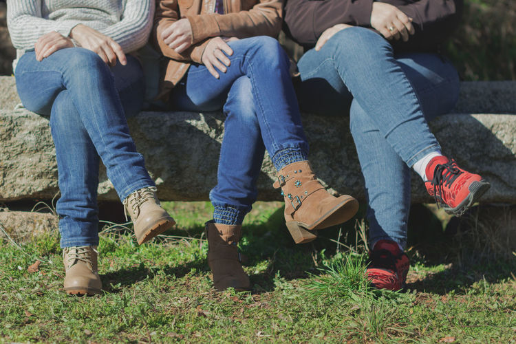 Low section of friends sitting on lawn
