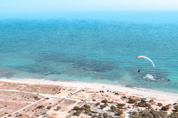 High angle view of person paragliding against sea