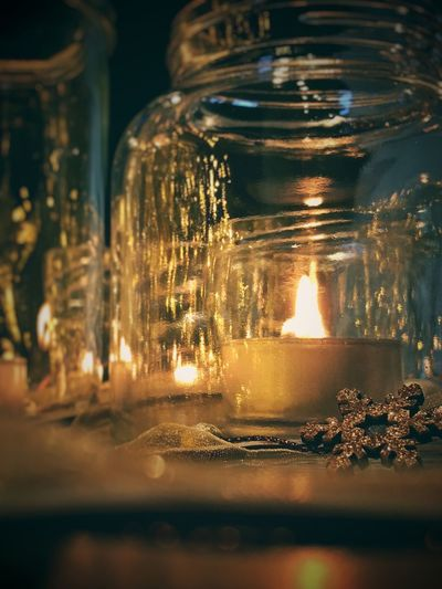 Low Angle View Of Candle In Glass Illuminated Candle Flame No People Indoors  Tea Light Burning Night Spirituality Close-up Surface Level Focus On Foreground Selective Focus Studio Shot Color Image Photography Vertical Christmas Shiny Decoration Candlelight Indoors  Dark Heat - Temperature Lighting Equipment