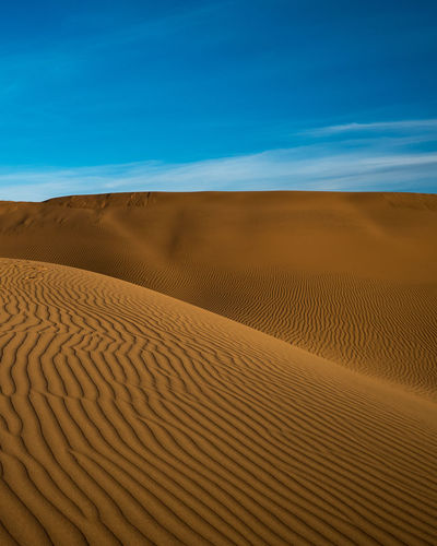 Sand dunes in desert against sky