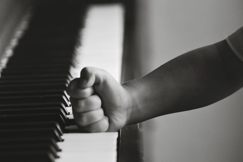Cropped Image Of Child Hand On Piano Key