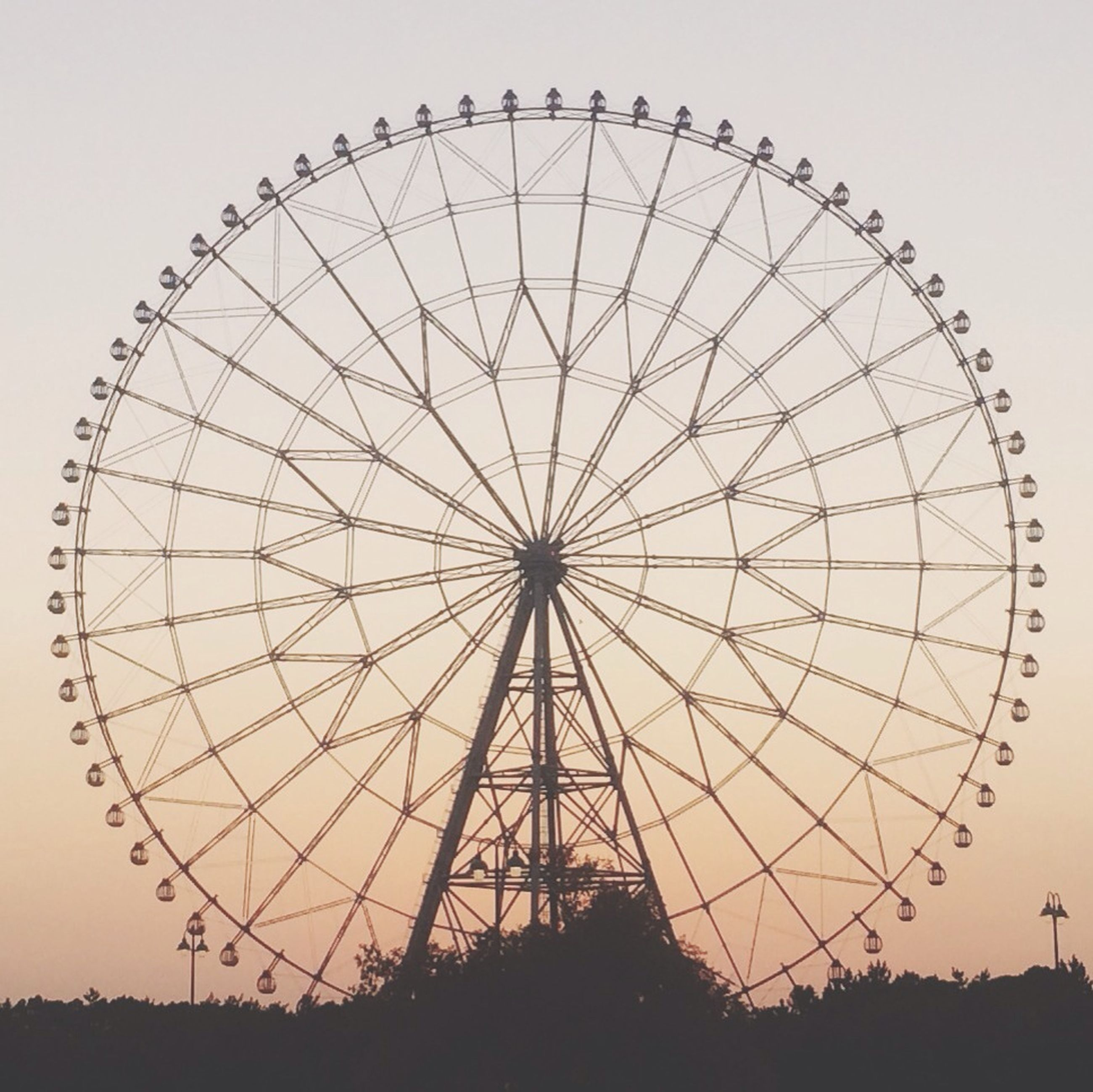 ferris wheel, amusement park, amusement park ride, arts culture and entertainment, low angle view, sky, circle, silhouette, clear sky, large, big wheel, fairground ride, fun, fairground, outdoors, built structure, enjoyment, day, no people, geometric shape