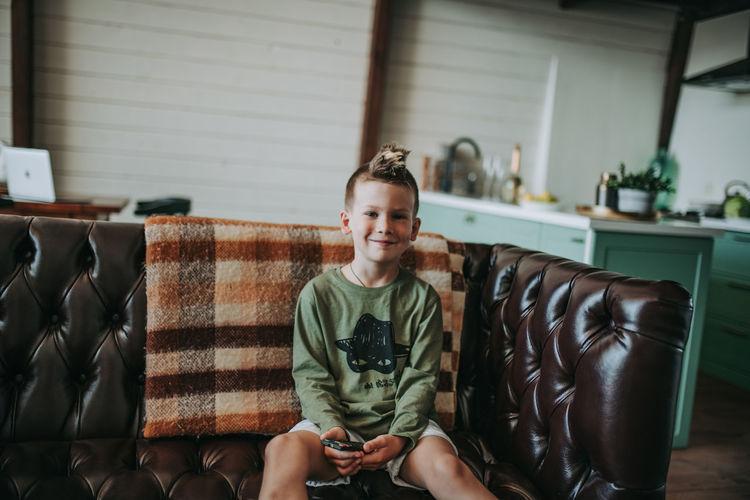 Portrait of smiling boy sitting on sofa