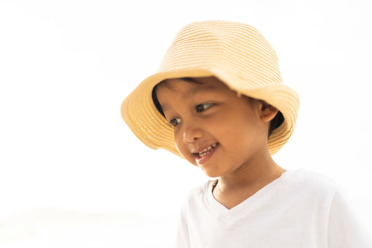 Close-up of boy wearing hat against clear sky in summer