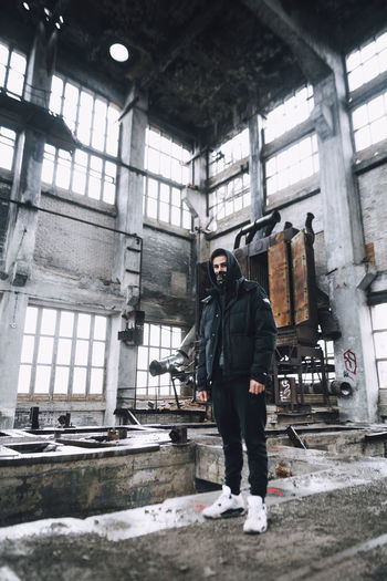 Full length portrait of young man standing in abandoned building