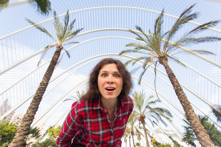 Surprised woman against palm trees