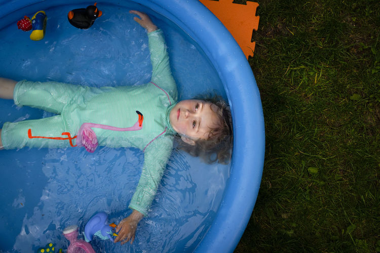 High angle view of girl lying in wading pool