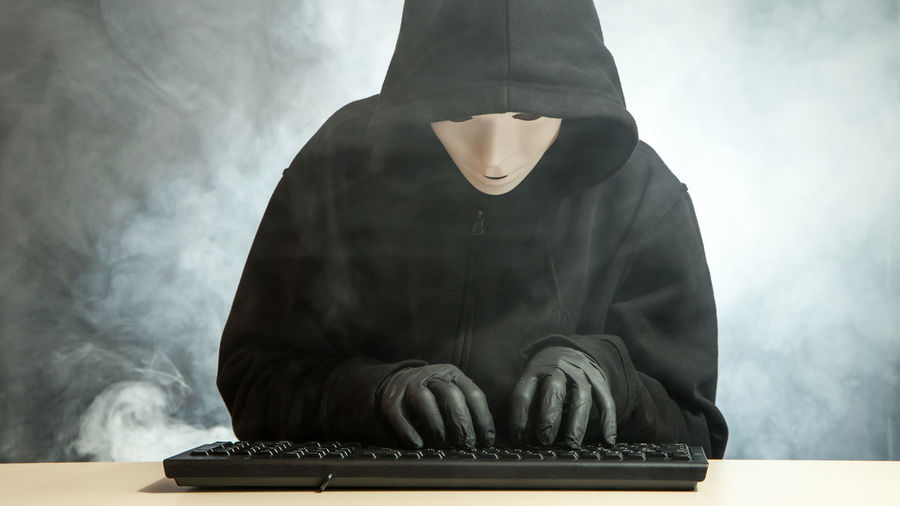 a computer hacker sits at a keyboard Crime Stealing Theft Burglar Code Computer Cyber Cyberspace Danger Data Hack Hacker Hacking Indoors  Information Internet One Person Password person Real People Spyware System Technology Typing Virus