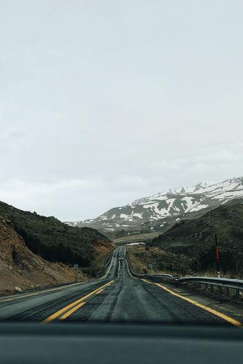 Road against sky seen through car windshield