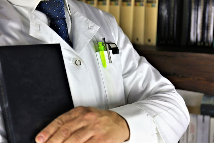 Midsection Of Scientist Holding Diary