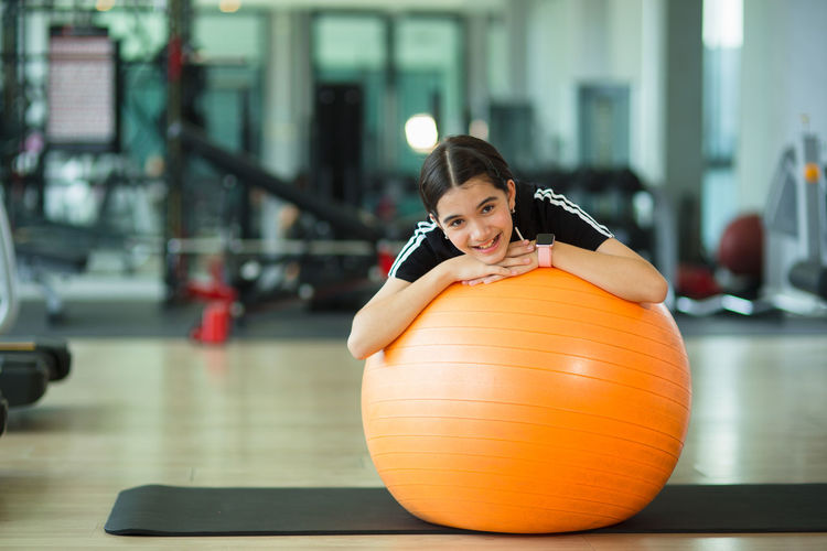 Portrait of smiling girl over fitness ball in gym